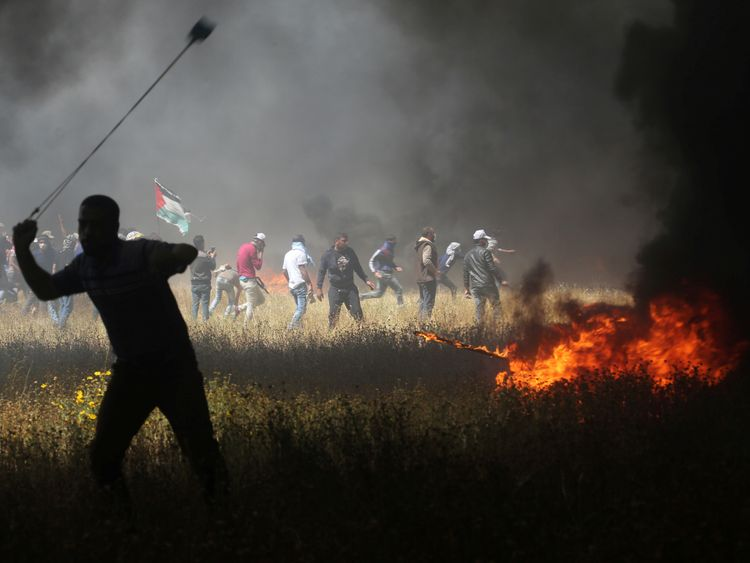 A Palestinian demonstrator uses a sling to hurl stones