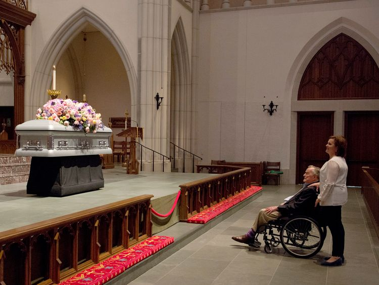 Former President George H. W. Bush looks at the casket with his daughter Dorothy
