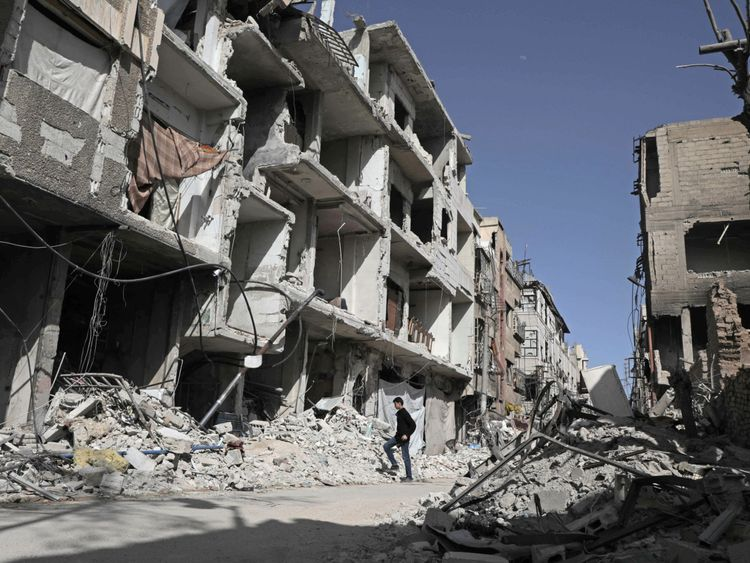 A Syrian man walks down a street past destroyed buildings on March 25, 2018, in Douma