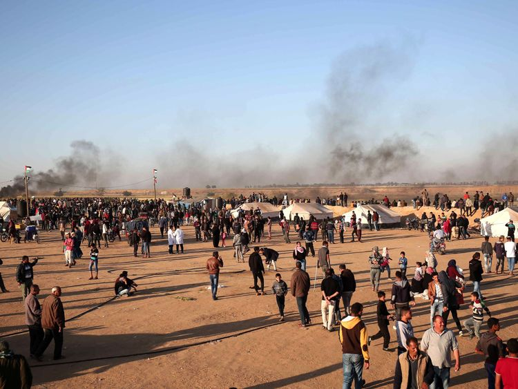 Palestinian protesters walk in a camp during clashes with Israeli security forces