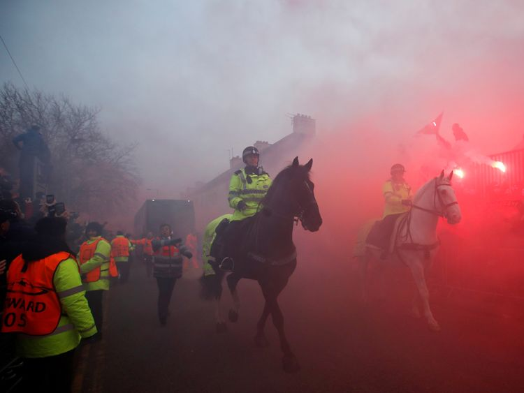 Police officers clear the road as Liverpool fans set off flares