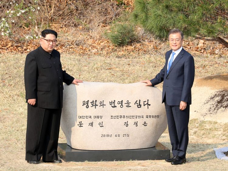 South Korean President Moon Jae-in and North Korean leader Kim Jong Un stand at a plaque after planting a commemorative tree