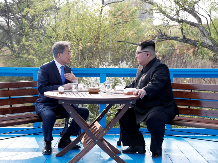 South Korean President Moon Jae-in and North Korean leader Kim Jong Un sit together at the truce village of Panmunjom