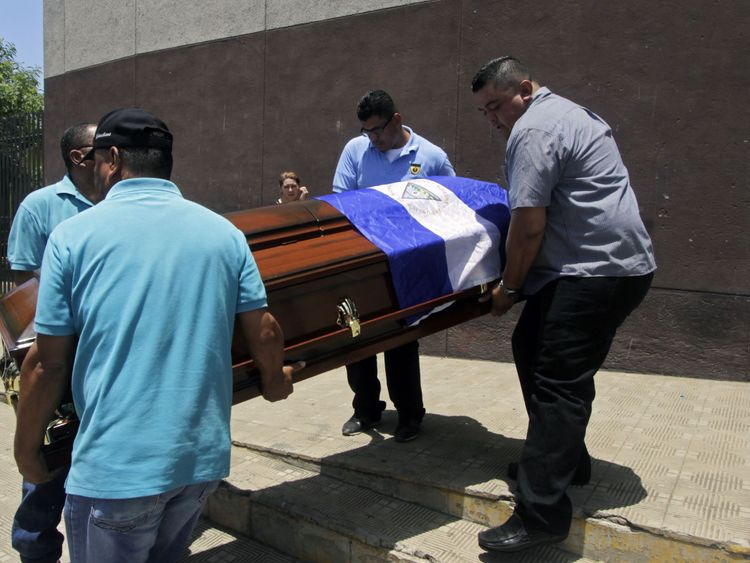 Men carry the coffin of Alvaro Conrado, 15, a high school student killed during a protest