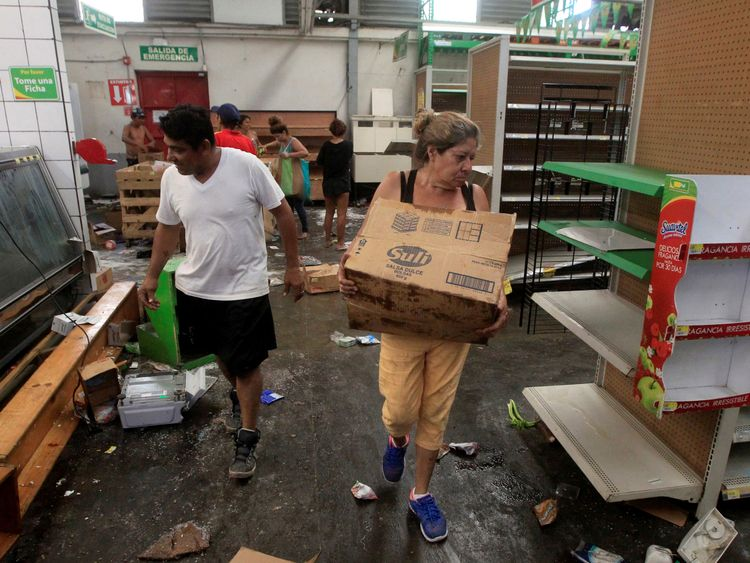 People with goods looted from a store in Managua