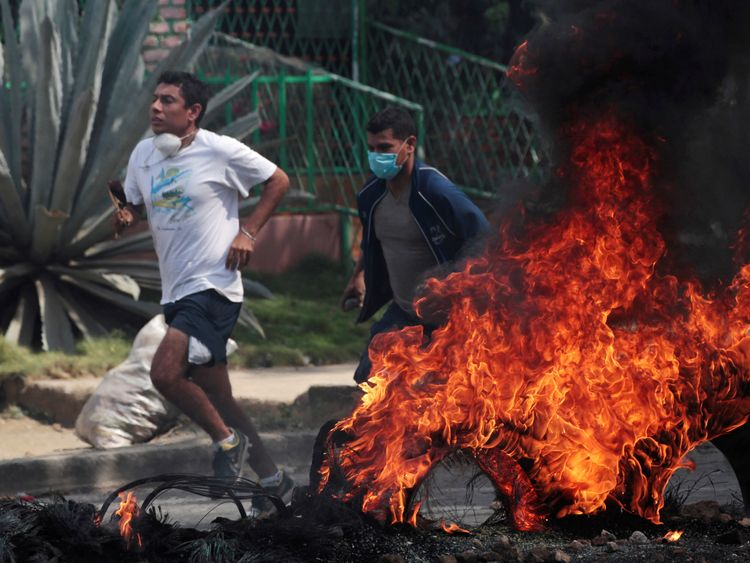 Demonstrators run past a burning barricade