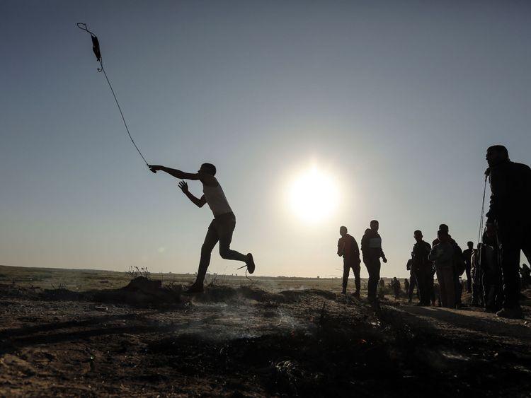 A Palestinian protester hurls stones toward Israeli soldiers