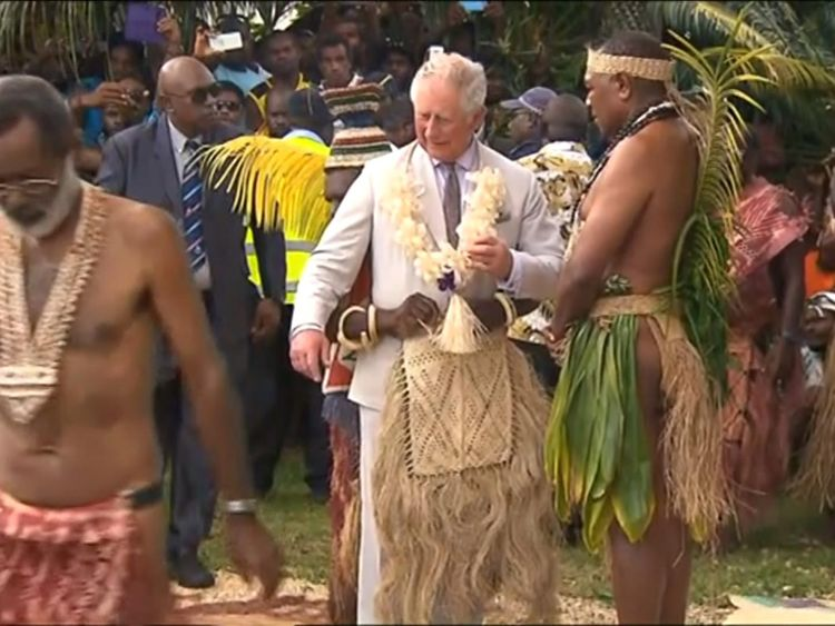 A Vanuatu islander appears to be fastening Charles' grass skirt during the ceremony