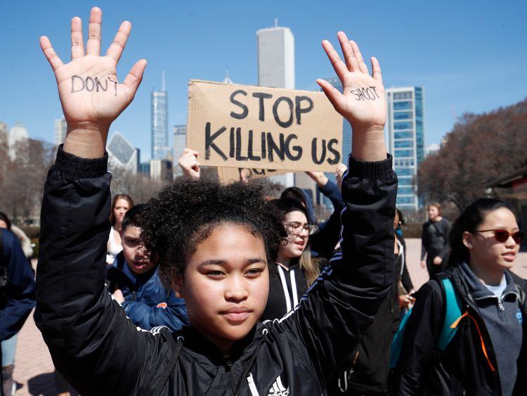A student holds up her hands while taking part in National School Walkout Day to protest school violence