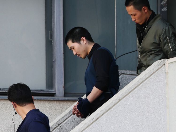 Tatsuma Hirao is escorted as he leaves a police department in Hiroshima