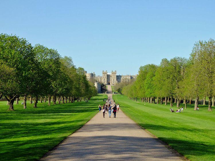 People enjoy the sunshine on the Long Walk at Windsor Castle in Berkshire