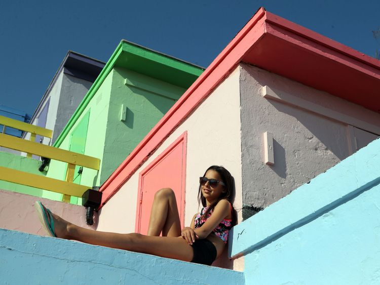 A woman enjoys the warm weather among the beach huts in Folkestone, Kent, on Friday