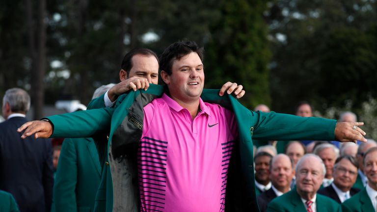 Patrick Reed receives the green jacket after winning the Masters in Augusta