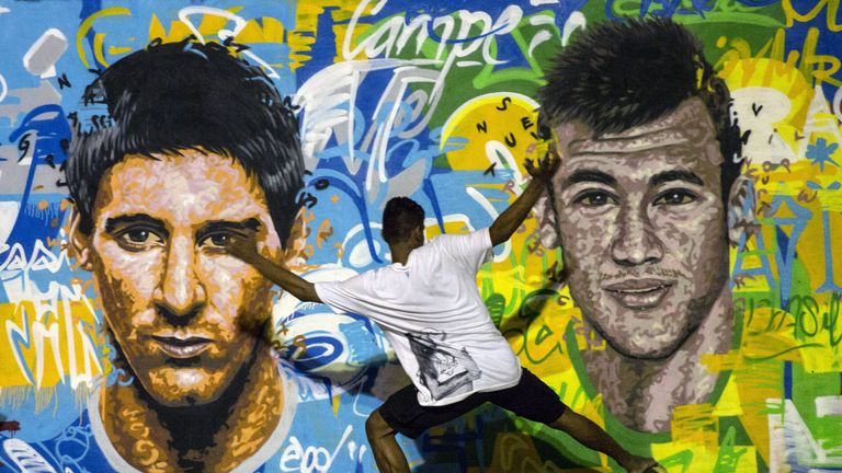 Youngsters play football in front of a mural of Argentine footballer Lionel Messi (L) and Brazil's Neymar