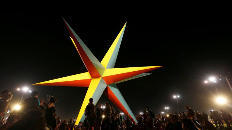 """Concertgoers sit around an installation called """"Supernova"""" at the Coachella Valley Music and Arts Festival in Indio"""