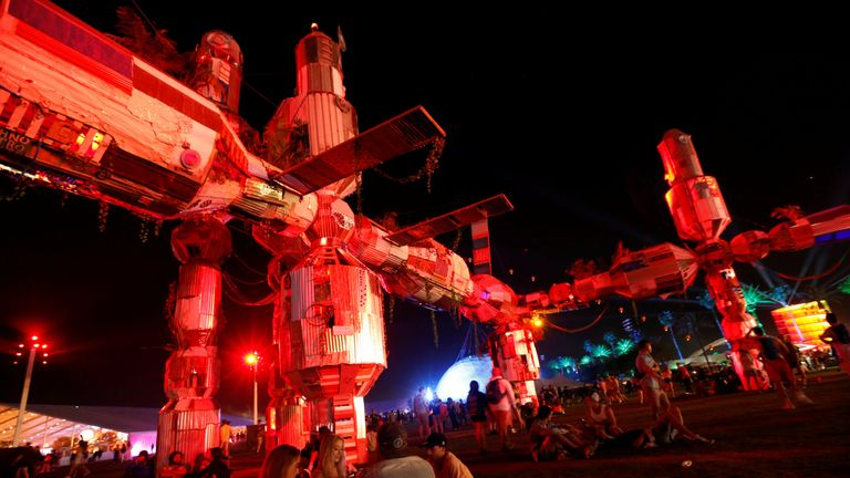 """Concertgoers sit by an installation called """"Palm-3 World Station"""" at the Coachella Valley Music and Arts Festival in Indio"""