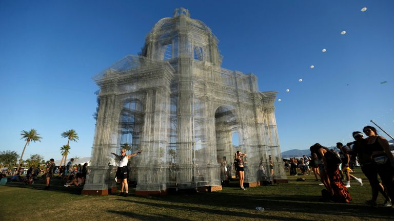 """People pose by an installation called """"Etherea"""" by Edoardo Tresoldi at the Coachella Valley Music and Arts Festival in Indio"""