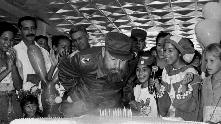 Fidel Castro blowing out birthday candles on his 70th birthday in 1996