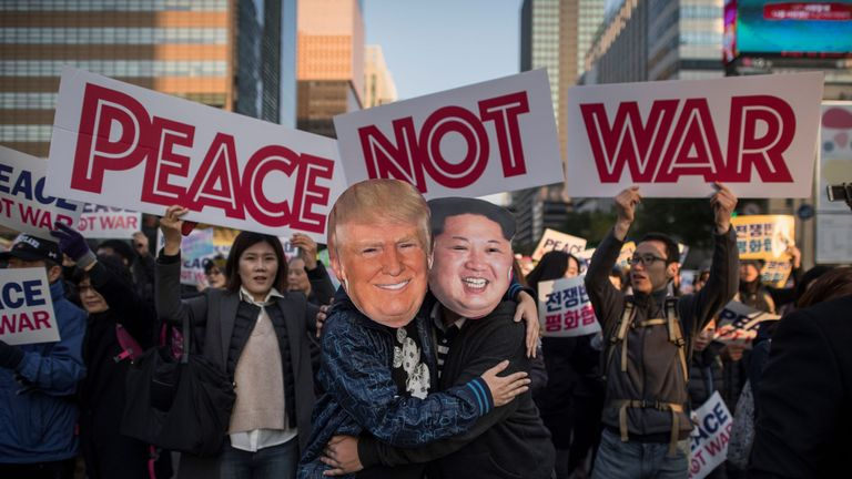 Demonstrators dressed as North Korean leader Kim Jong-Un and US President Donald Trump embrace during a peace rally in Seoul on November 5 2017