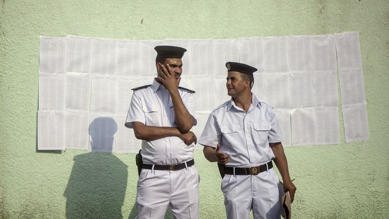 Egyptian police stand near a list of names of voters outside a polling station in Cairo on May 26, 2014