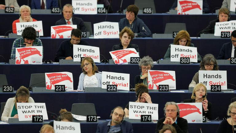 Members of the European Parliament hold placards 'Stop the War in Syria' as French President Emmanuel Macron delivers a speech
