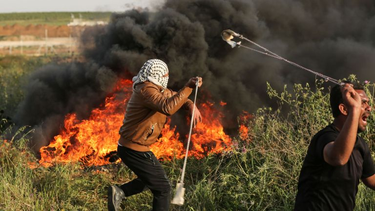 Palestinian protesters use slingshots to throw stones during clashes with Israeli forces