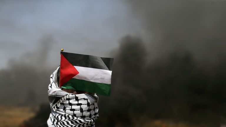 A demonstrator with a Palestinian flag looks on during clashes with Israeli troops