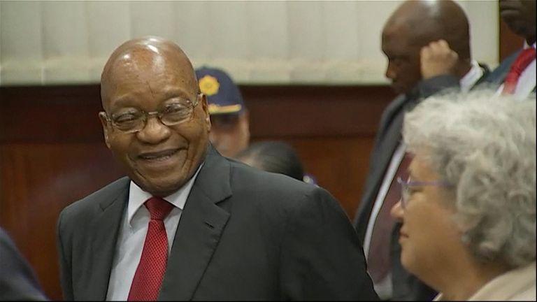 Mr Zuma shares a joke with his defence team