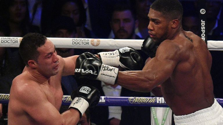 Anthony Joshua (R) aims a jab at Joseph Parker (L) in the final round of their heavyweight unification fight in Cardiff