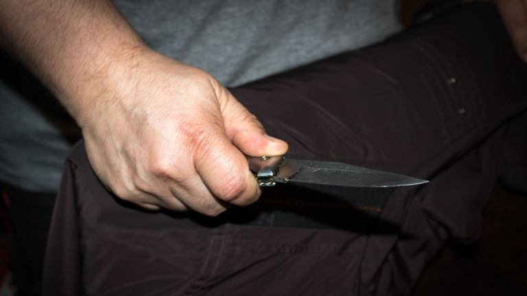 STOCK PHOTO: Closeup of a young man hand, holding a knife, about to attack,