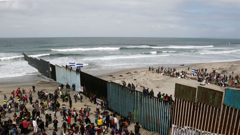 Asylum seekers stand on the Mexican side of the fence while their supporters cheer them on the US side