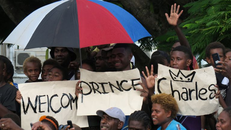 Well-wishers hold a welcome sign for Prince Charles as he visits the seafront of Port Vila, Vanuatu, on April 7 2018