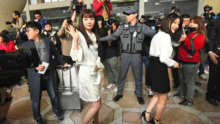 Members of Red Velvet wave to the media as they leave South Korea