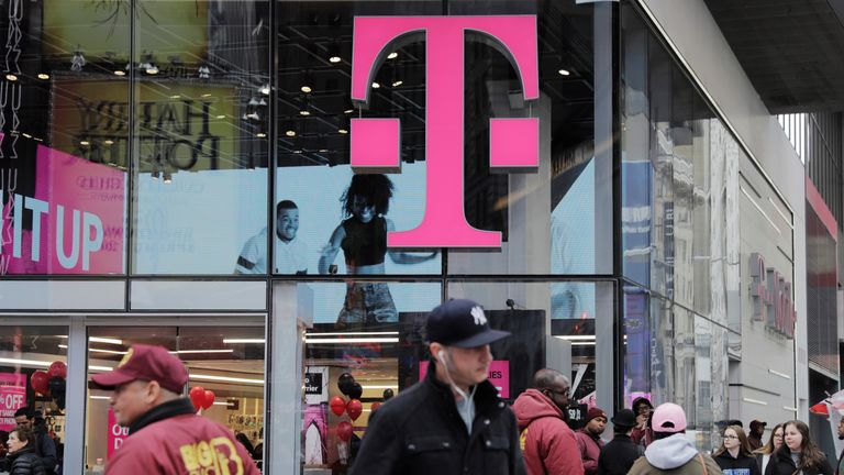 Pedestrians walk past a T-Mobile store in New York, U.S., April 27, 2018