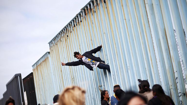 A man climbs the border fence in support of the hundreds of Central American migrants