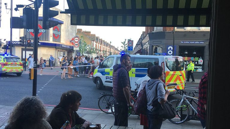Police outside Tooting Bec Underground station in south London, where two men were stabbed after a fight at rush hour