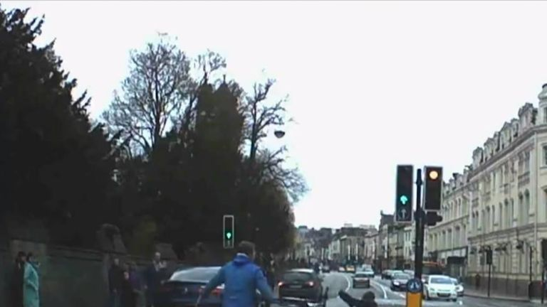 This dashcam video shows the moment two members of the public tackled a man, said to have been carrying a hunting knife, as he was fleeing police on a bicycle in central Cardiff, Wales, on April 15.