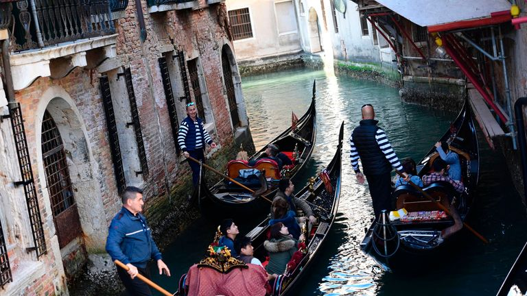 Tourists sit in gondolas on the Grand Canal in Venice