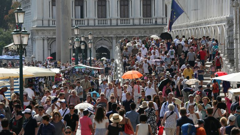 Tourists walk near St. Mark's Square in Venice, Italy, August 3, 2017