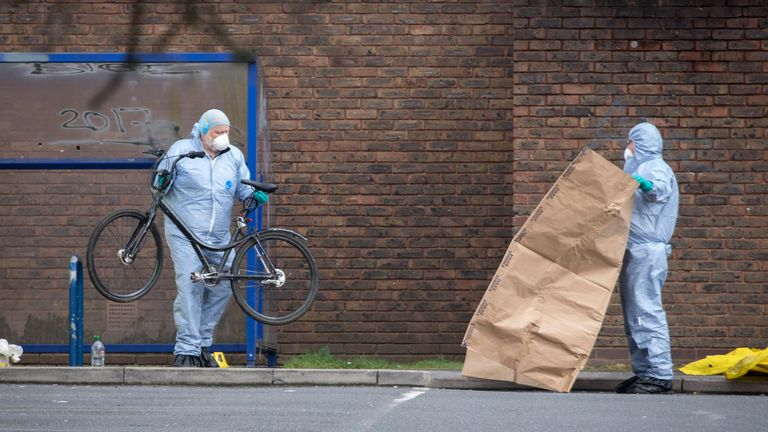 Forensic officers remove a bikefrom the  scene where the 16-year-old was shot
