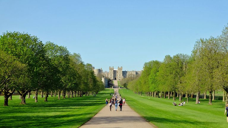 People enjoy the sunshine on the Long Walk at Windsor Castle in Berkshire