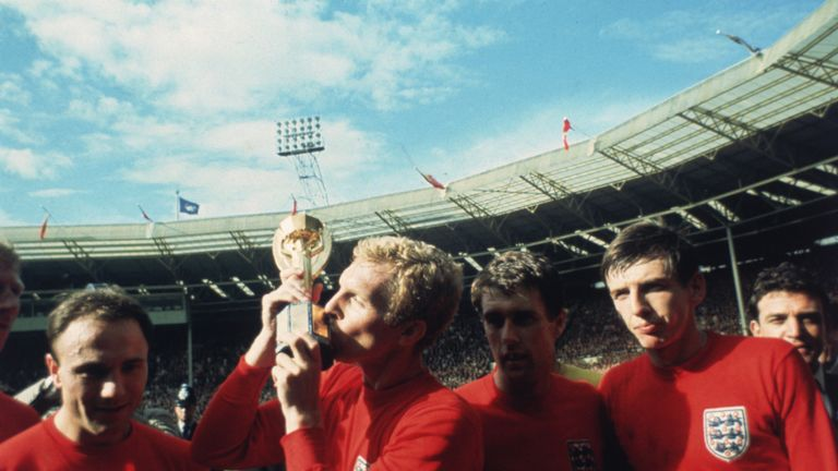 1966: England captain Bobby Moore kissing the Jules Rimet trophy as the team celebrate winning the 1966 World Cup final against Germany