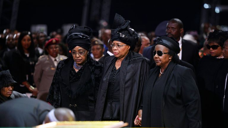 Winnie Mandela (L), and Nelson Mandela's widow Graca Machel (C), stand by his coffin in 2013