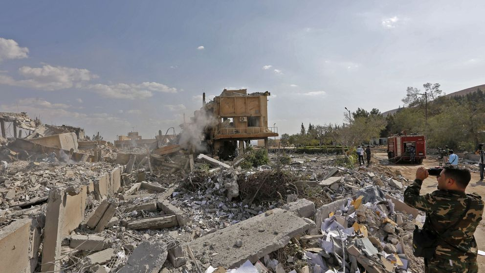 A Syrian soldier takes a picture of the wreckage of the research centre