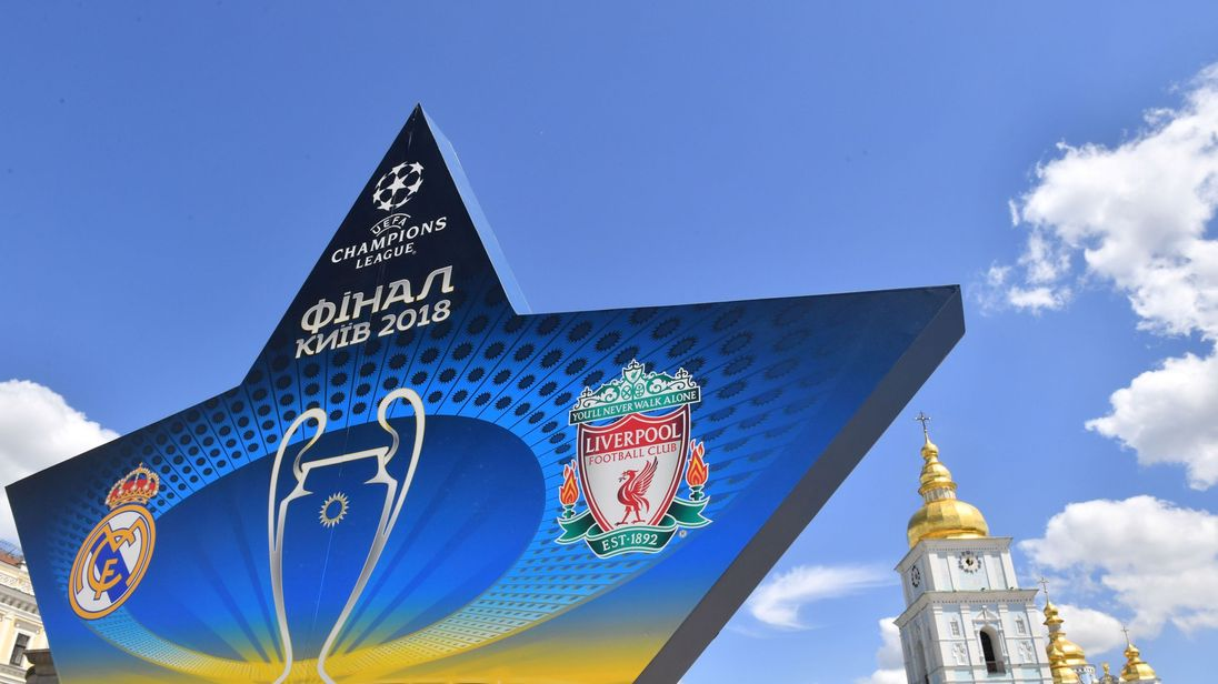 A woman takes a picture as she walks past a star shaped billboard announcing the 2018 UEFA Champions League final in the city centre of Kiev