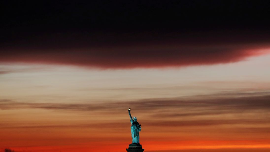 The sun sets behind the Statue of Liberty after a rain storm in New York, U.S