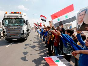 Children wave national flags and carry portraits of Syrian president Bachar al-Assad on the highway extending from Harasta in Eastern Ghouta on the outskirts of Damascus to the northern part of Syria, after it reopened to traffic on May 15, 2018