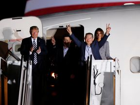Two of the Americans formerly held hostage in North Korea gesture next to Donald Trump and first lady Melania Trump, upon their arrival at Joint Base Andrews