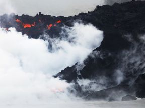 Steam rises as lava enters the Pacific Ocean at dawn