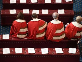 LONDON, ENGLAND - JUNE 21:  Peers find their places in the House of Lords before the State Opening Of Parliament at Houses of Parliament on June 21, 2017 in London, England. This year saw a scaled-back State opening of Parliament Ceremony with the Queen arriving by car rather than carriage and not wearing the Imperial State Crown or the Robes of State.  (Photo by Carl Court - WPA Pool/Getty Images)